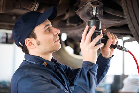 Portrait eines Mechanikers ein Auto in seiner Garage reparieren