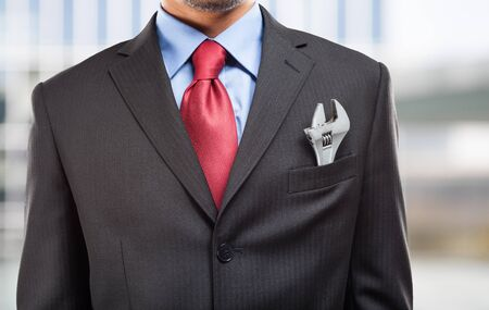 pocket: Businessman keeping an adjustable wrench in his pocket