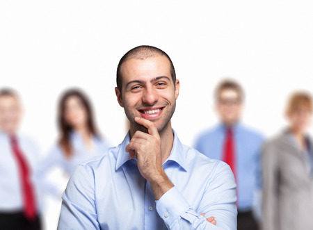 likeable: Portrait of a young smiling man in front of a group of people
