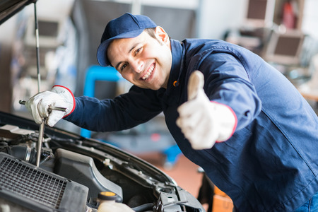 motor: Portrait of an auto mechanic at work on a car in his garage Stock Photo
