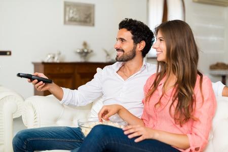 Glückliche lächelnde Paare, die fernsehen. Geringe Schärfentiefe, Fokus auf den Mann