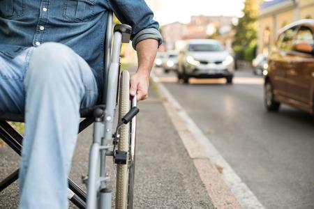 paraplegic: Detalle de un hombre que usa una silla de ruedas en una calle urbana