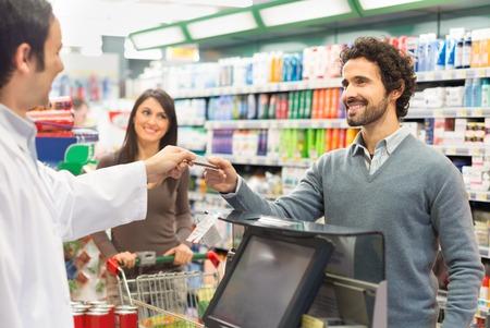 Cliente utilizzando una carta di credito per pagare in un supermercato