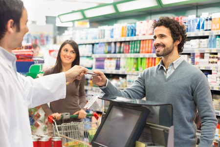 paying: Customer using a credit card to pay in a supermarket