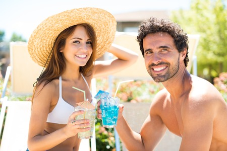 bikini couple: Portrait of a beautiful young couple enjoying a cocktail while talking