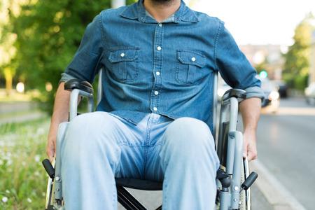 paraplegico: Detalle de un hombre que usa una silla de ruedas en una calle urbana