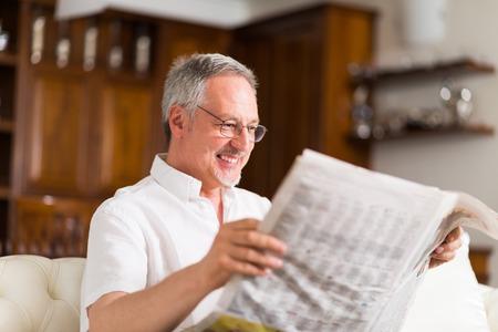 Portrait of a mature man reading a newspaper