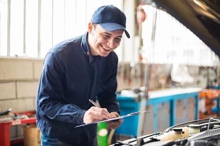 mot: Portrait of a mechanic writing on a clipboard