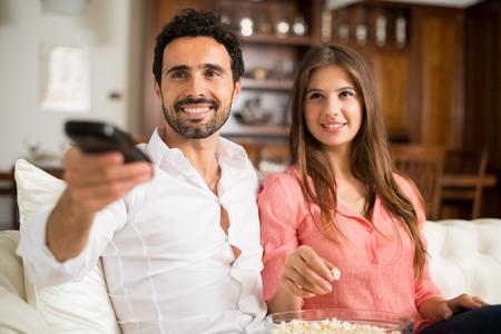 pareja viendo television: Pareja joven que se prepara para ver una película Foto de archivo
