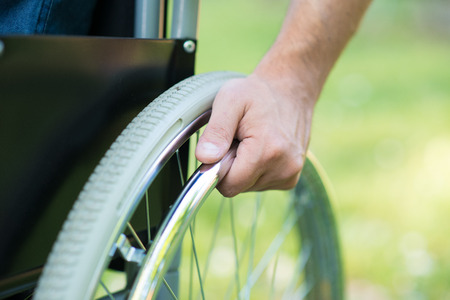 medical equipment: Detail of a man using a wheelchair in a park