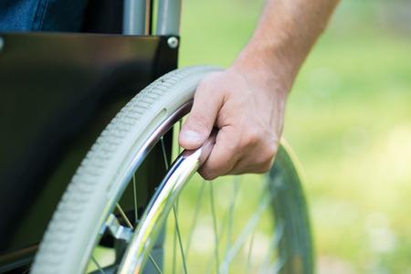 persona en silla de ruedas: Detalle de un hombre que usa una silla de ruedas en un parque