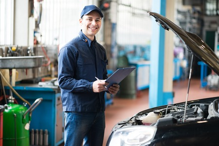upkeep: Smiling mechanic holding a clipboard in front of a car