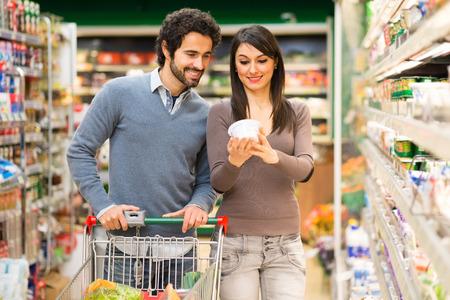 tiendas de comida: Pareja joven de compras en un supermercado