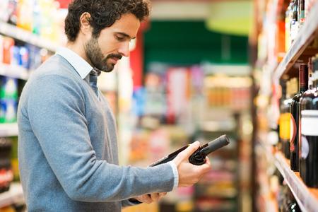 wine drinking: Man in a supermarket choosing a wine