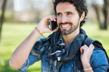 calling on phone: Portrait of a smiling man talking on the phone