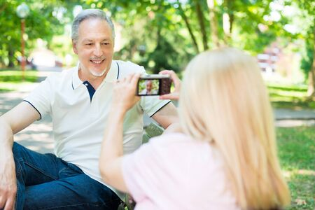 compact camera: Wife using a compact camera to take a portrait of her husband in a park Stock Photo