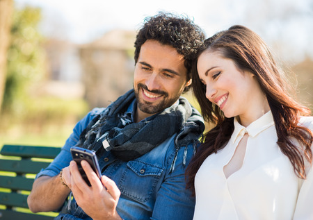 happy couple: Smiling man showing his mobile phone to a girl