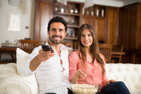 couple watching tv: Happy smiling couple watching tv. Shallow depth of field, focus on the man