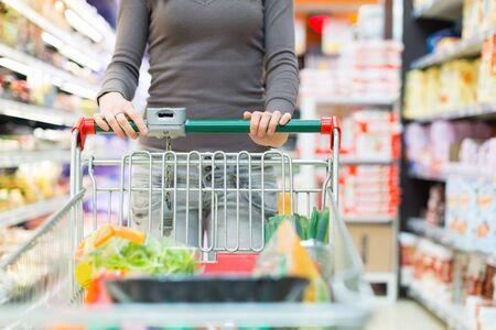 Mulher que empurra um carrinho de compras em um supermercado
