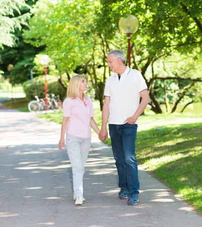 parejas caminando: Feliz pareja madura caminando en un parque mientras mantiene las manos Foto de archivo