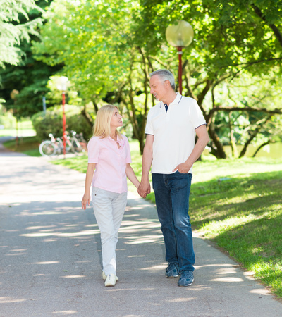 holding hands while walking: Happy mature couple walking in a park while holding hands