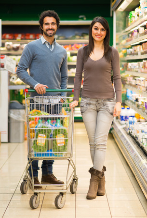 shopping trolley: Young couple shopping in a supermarket