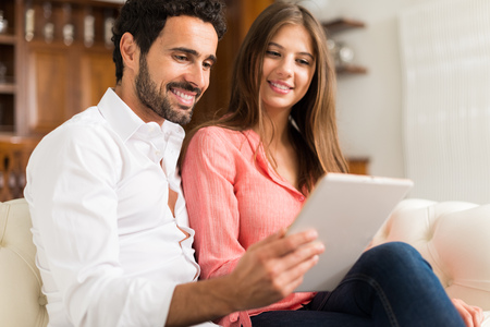 luxury apartment: Portrait of an happy couple using a tablet. Shallow depth of field, focus on the man