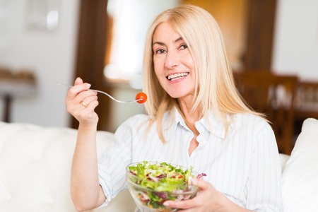 vegetable salad: Portrait of a smiling woman eating an healthy salad in her living room Stock Photo