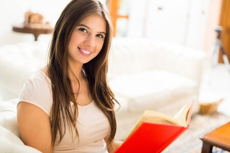 a long poem: Young smiling woman reading a book in her house
