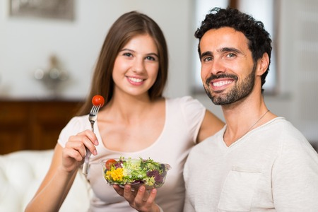 salad fork: Couple eating a salad in the living room Stock Photo