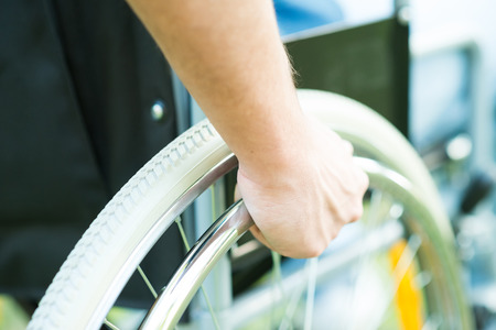 Close-up of male hand on the wheel of a wheelchair