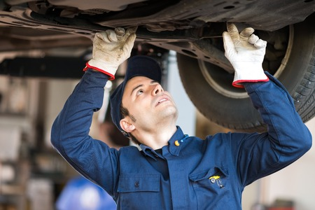 auto repair: Portrait of a mechanic checking the condition a lifted car
