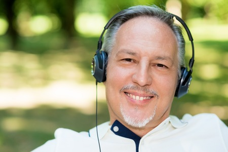 escucha activa: Portrait of a mature smiling man listening music outdoors
