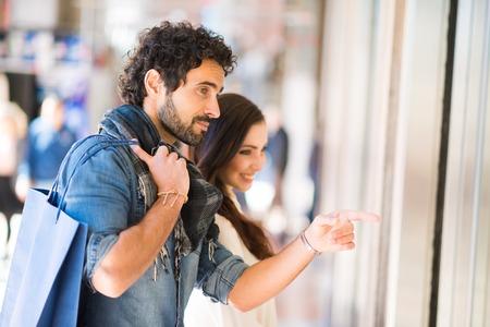 Junge lächelnde Paare Einkaufsmöglichkeiten in einer städtischen Straße. Geringe Schärfentiefe, Fokus auf den Mann