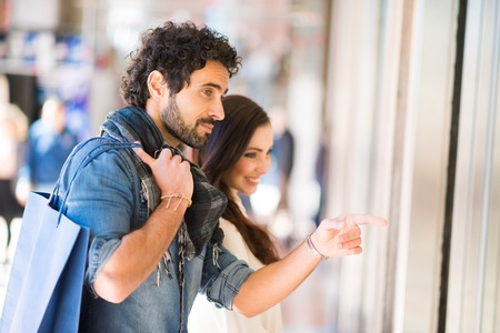 clothing shop: Young smiling couple shopping in an urban street. Shallow depth of field, focus on the man