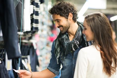 etiquetas de ropa: Compras Pareja feliz en una tienda de ropa
