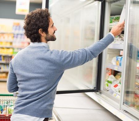alimentos congelados: Hombre que toma profunda de alimentos congelados de un congelador en un supermercado Foto de archivo
