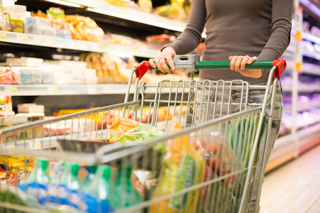 woman shopping cart: Close-up detail of a woman shopping in a supermarket Stock Photo