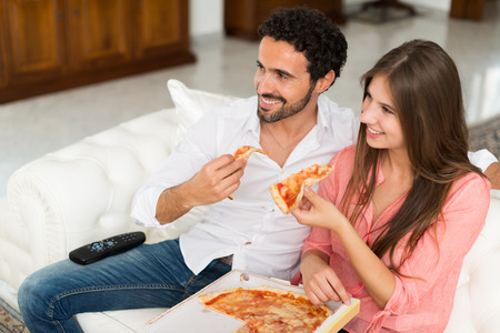 eating: Happy couple watching tv while eating pizza. Shallow depth of field, focus on the man