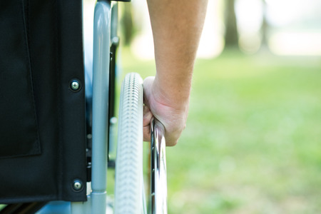 persona enferma: Detalle de un hombre que usa una silla de ruedas en un parque
