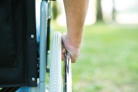 silla de ruedas: Detalle de un hombre que usa una silla de ruedas en un parque
