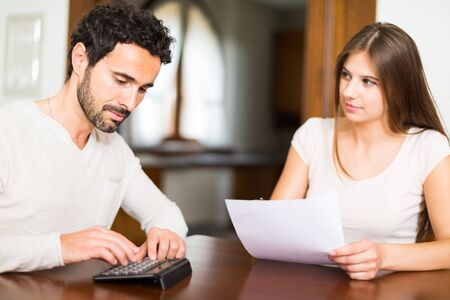 economic rent: Young couple calculating their expenses. Shallow depth of field, focus on the man