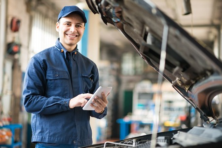 body shop: Mechanic using a tablet in his garage Stock Photo
