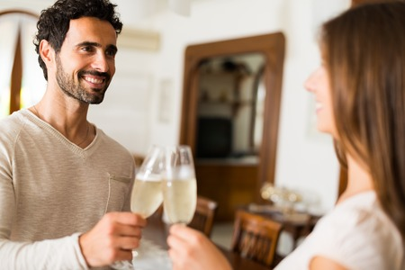 champagne flutes: Couple toasting champagne flutes in their apartment. Shallow depth of field, focus on the man