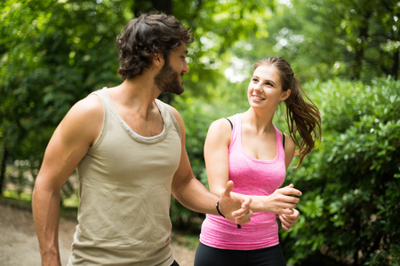 jog: Couple running in a park. Shallow depth of field, focus on the woman Stock Photo
