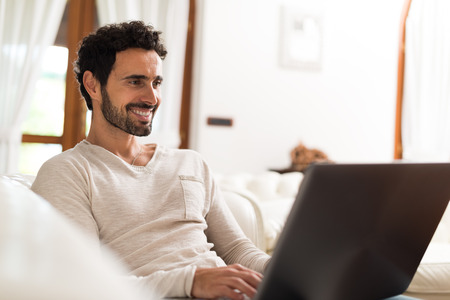 emails: Portrait of a smiling young woman using a tablet computer in her apartment