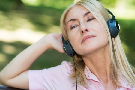radio active: Portrait of a mature woman listening music outdoors