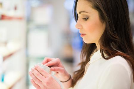 productos de belleza: Retrato de una mujer de compras en una tienda de belleza