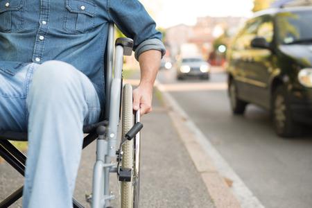 Detail of a man using a wheelchair in an urban street