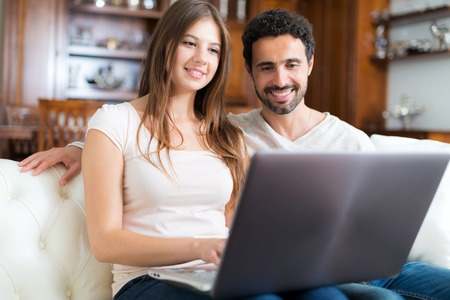luxury apartment: Portrait of an happy couple using a laptop computer in their house. Shallow depth of field, focus on the woman
